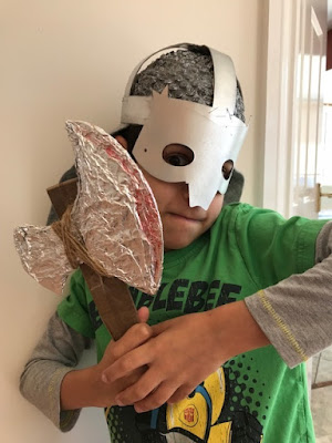 Child with homemade Viking helmet and axe
