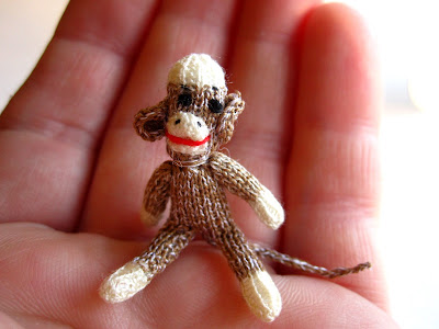 1/12th scale hand knitted sock monkey sitting on a hand