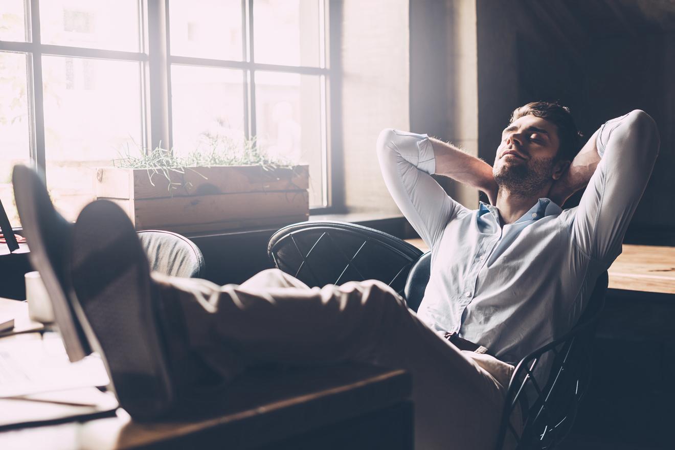 Mann entspannt im Büro mit Füßen auf dem Schreibtisch