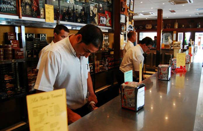 Barra con camareros de La Flor de Toranzo, montaditos cántabros en Sevilla