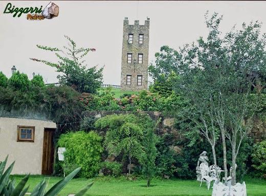 Vista da torre de pedra com os muros de pedra com a execução do paisagismo.
