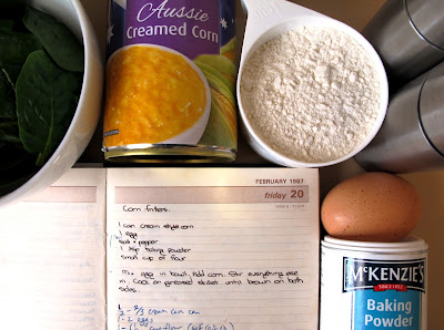 Handwritten recipe for corn fritters, surrounded by the ingredients needed to cook the recipe