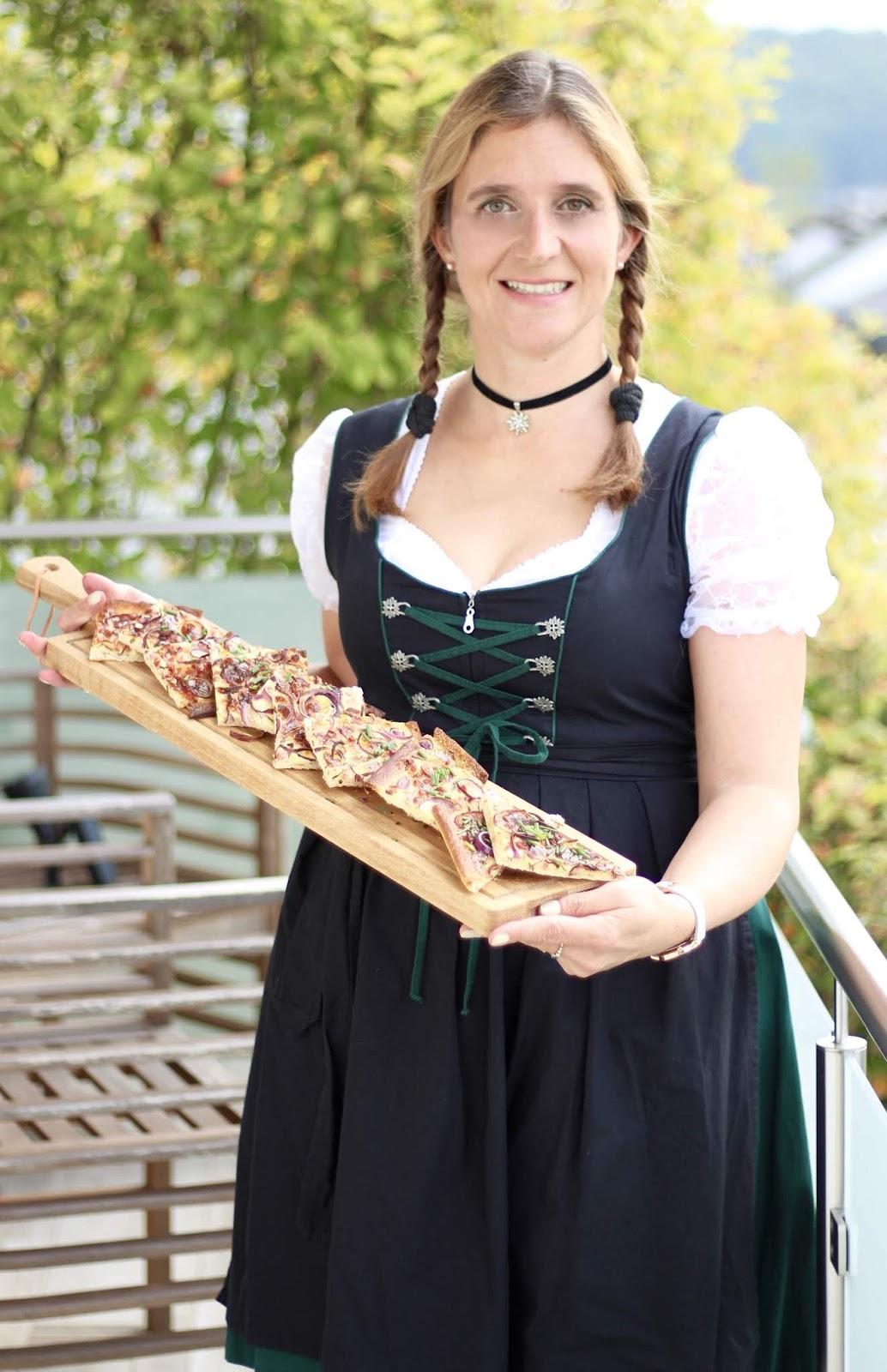 Yushka präsentiert den bayerischer Zwiebelkuchen im Dirndl
