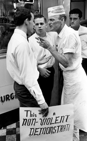 """Archie Allen, left, a member of the civil rights demonstrators, talks with employees of the Tic Toc Restaurant on downtown Church Street April 27, 1964. Moments later, Allen was attacked by the employees and knocked down on the sidewalk."""