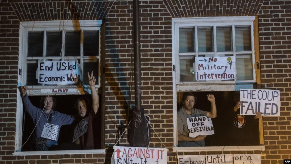 Los activistas son vistos posando en la ventana de la embajada venezolana ocupada después de que agentes federales llegaron para abrir la puerta en Washington, el 13 de mayo / AFP