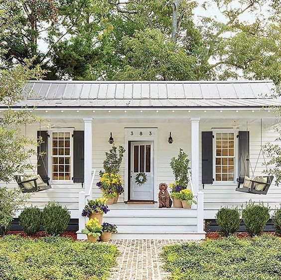 White ranch with two porch swings on front porch  beautiful home exterior seen on Hello Lovely Studio
