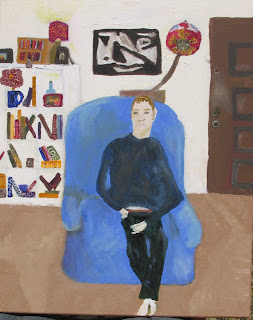 Disabled man sitting in blue armchair wearing sweats and looking contemplative. Bookcase with different color books and the door to the room are behind him. On the wall behind him are a picture and a hanging light.