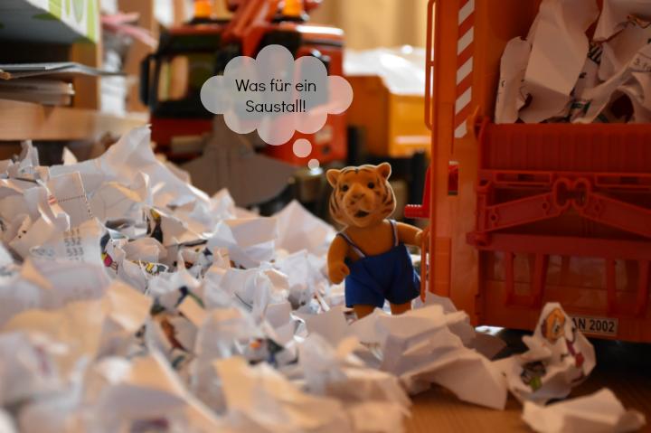 Spielzeug-Tiger mit Bruder Müllauto im Papiermist