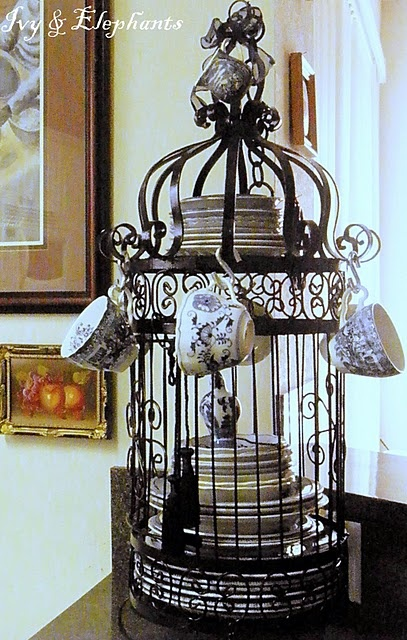 this vintage bird cage doubles as storage for fine china and tea cups
