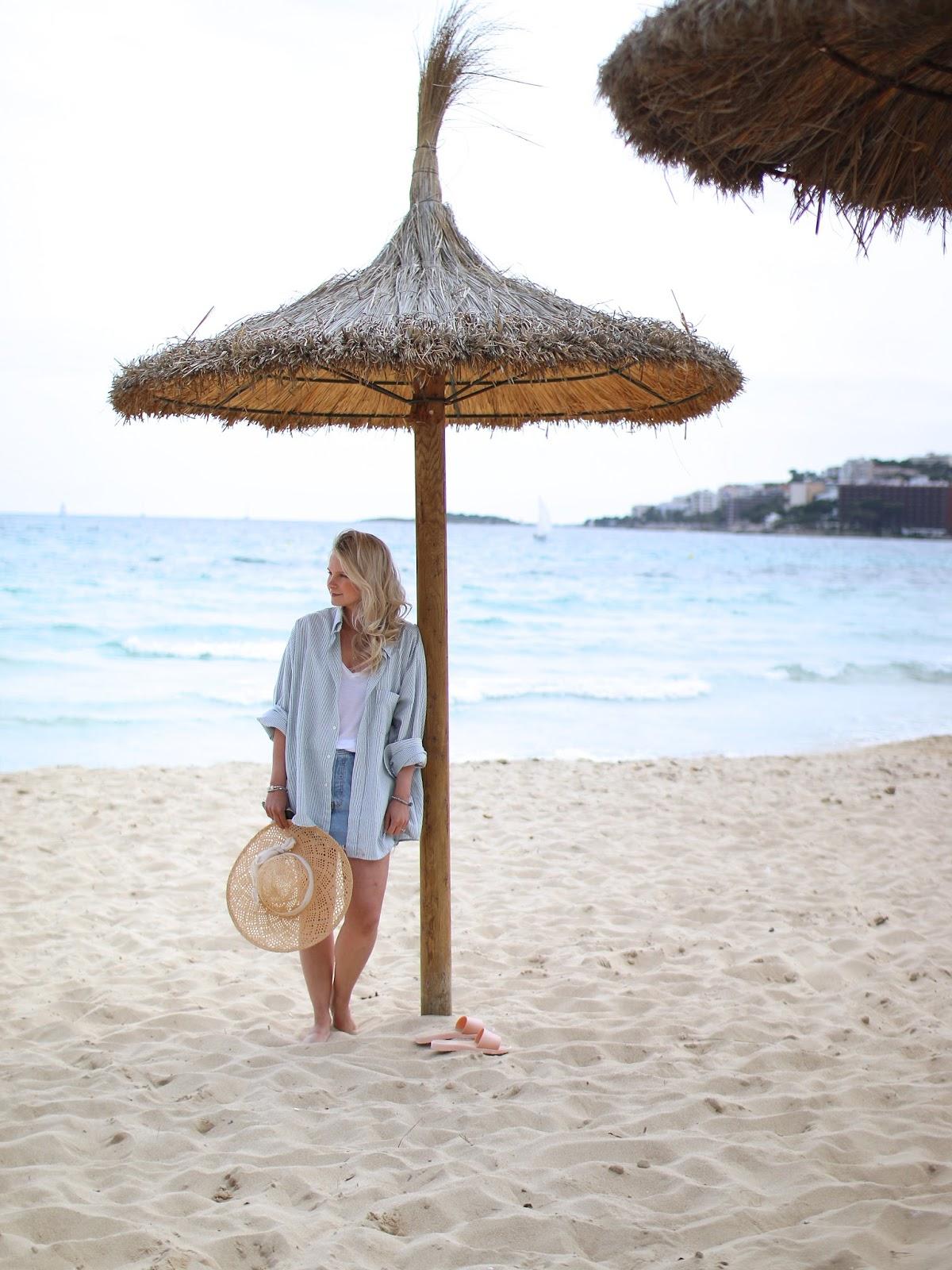 a women wearing a vintage denim cutoff skirt standing under a hut on the a beach in spain