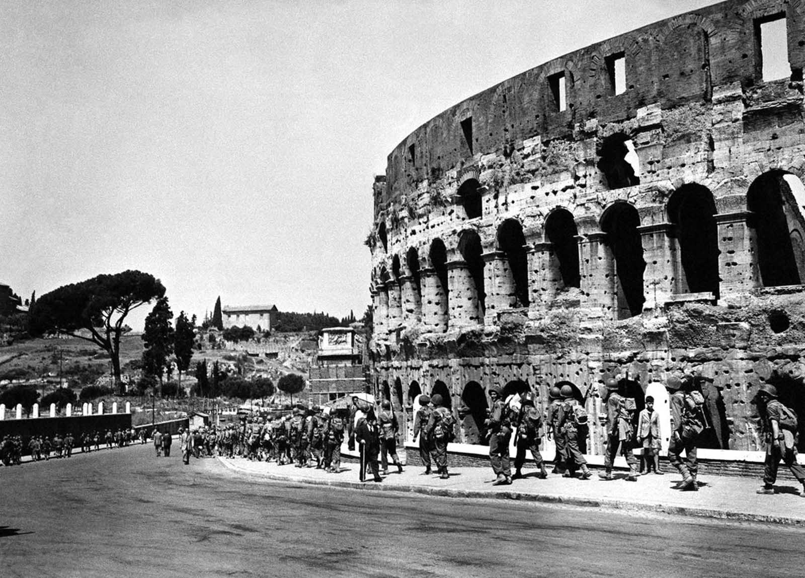 U.S. soldiers march past the historical Roman Colosseum and follow their retreating enemy in Rome, Italy, on June 5, 1944.