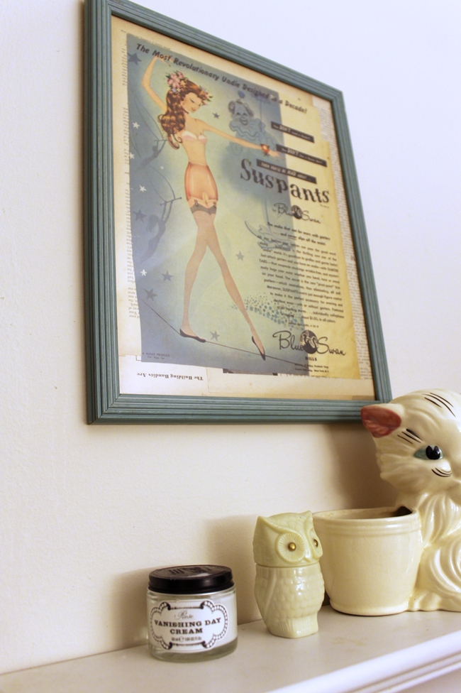 vintage 1940s suspants girdle ad hanging in a vintage bathroom with vintage kitty planter, owl perfume bottle and cold cream