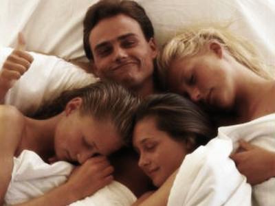 Homem com três mulheres na cama