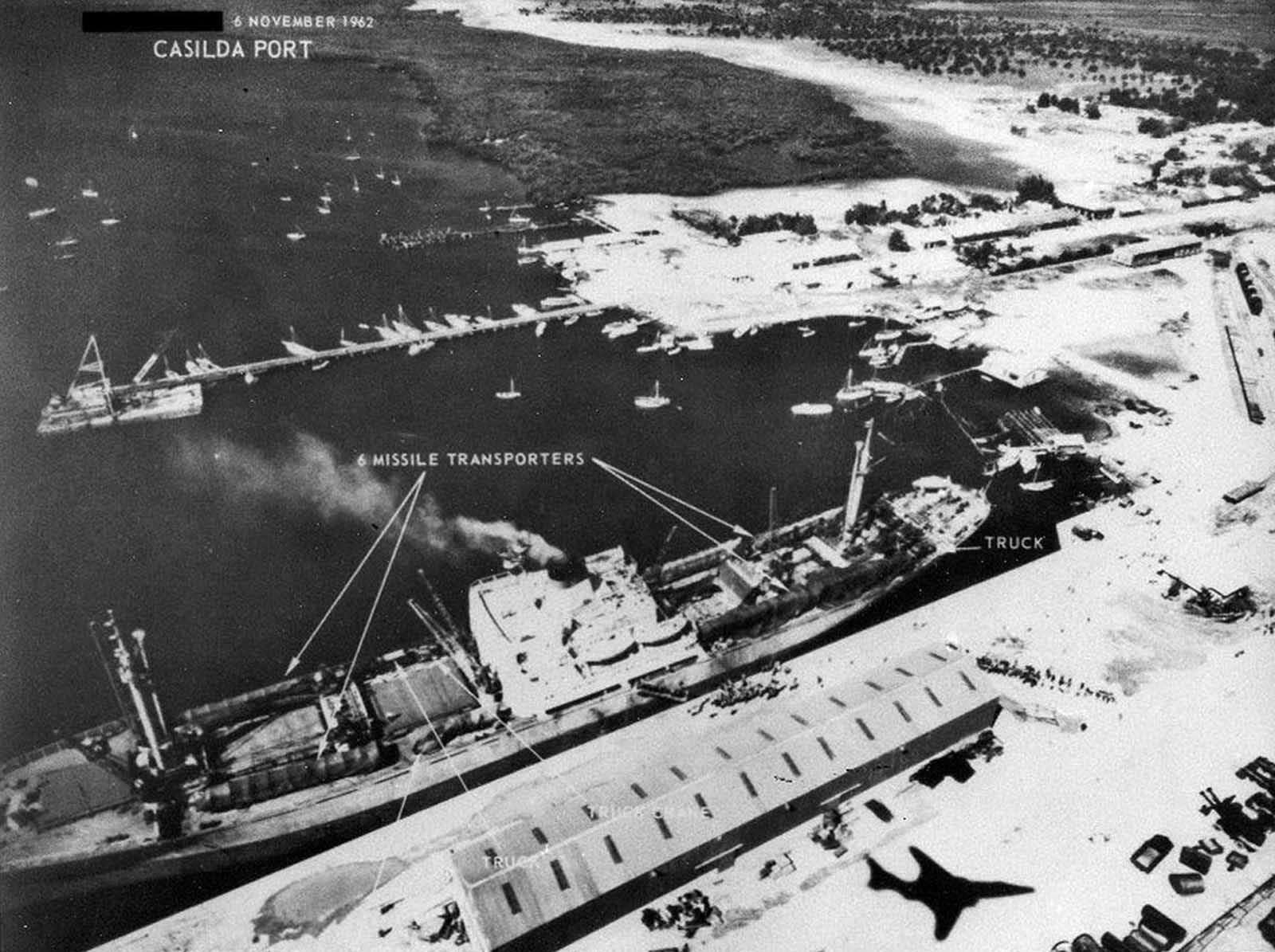 Soviet personnel and six missile transporters loaded onto a Soviet ship in Cuba's Casilda port, on November 6, 1962. Note shadow at lower right of the RF-101 reconnaissance jet taking the photograph.