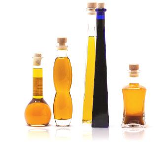 4 frascos compridos com óleos de cor amarela e uma garrafa comprida azul, todas fechadas com rolha.