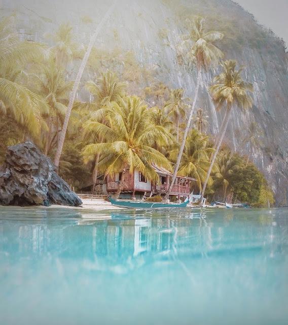 Foto de una cabaña a orillas de un mar turquesa con un fondo de palmeras en Filipinas