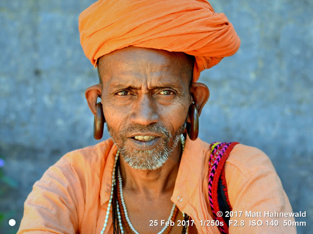 matt hahnewald photography; facing the world; gorakh nath; monk; monastery; bhavnath; bhavnath fair; character; face; earrings; ears; holed; eyes; facial expression; eye contact; stubbly; turban; orange; consent; empathy; rapport; respect; traveling; religious; traditional; cultural; hinduism; festival; event; mela; devotee; pilgrim; junagadh; gujarat; asian; indian; western india; one person; male; elderly; man; picture; photo; face perception; physiognomy; educational; nikon d3100; nikkor af-s 50mm f/1.8g; prime lens; 50mm lens; 4x3 aspect ratio; horizontal orientation; street; portrait; closeup; headshot; full-face view; outdoors; color; posing; authentic; smiling; determined; focused; manly; kanphata; yogi; darshani; gorakhnathi; shaivism; splitted ears