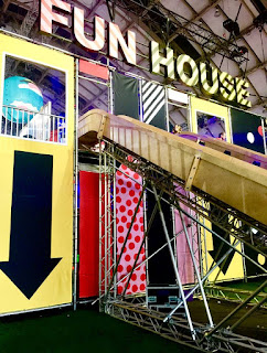 A stand containing a bright stone coloured slide with different coloured steps and yellow arrows on the side with FUN HOUSE in bold silver letters above on a bright background.