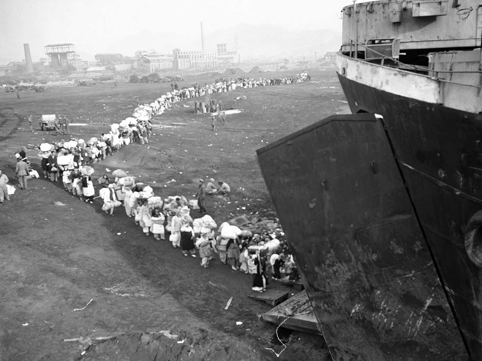 A long winding stream of Korean refugees board a vessel in Hungnam harbor, North Korea on December 21, 1950, as they flee the advancing Chinese Communists and North Koreans.