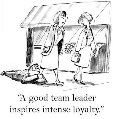 "Cartoon of wo women walk along the street. One has a man hanging on to her ankle. She explains to the other: ""A good team leader inspires intense loyalty."""