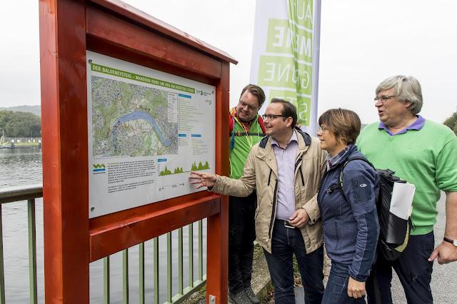 Vier Wanderer betrachten eine der Infotafeln am Wegesrand (Hier: Baldeneysee)