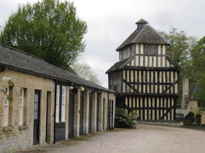 A one-storey stone coach house or garage and three storey half-timbered building