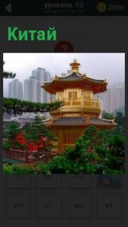 Китайское архитектурное национальное здание на фоне современного города с зелеными насаждениями вокруг