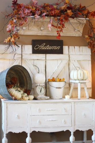 This autumn themed area with leaves, corn, a silver bucket and pumpkins is rustic.