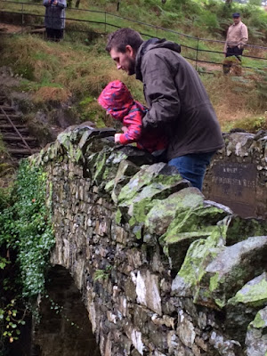 Daddy standing on a stone bridge holding up toddler to look over it