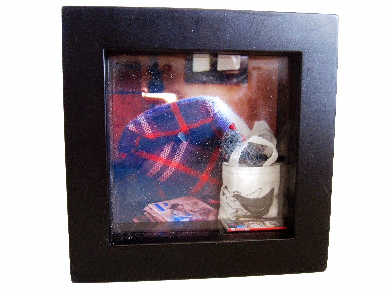 A box picture frame containing a photo of a modern miniature scene, and a miniature knitting bag and book included in front of the photo.