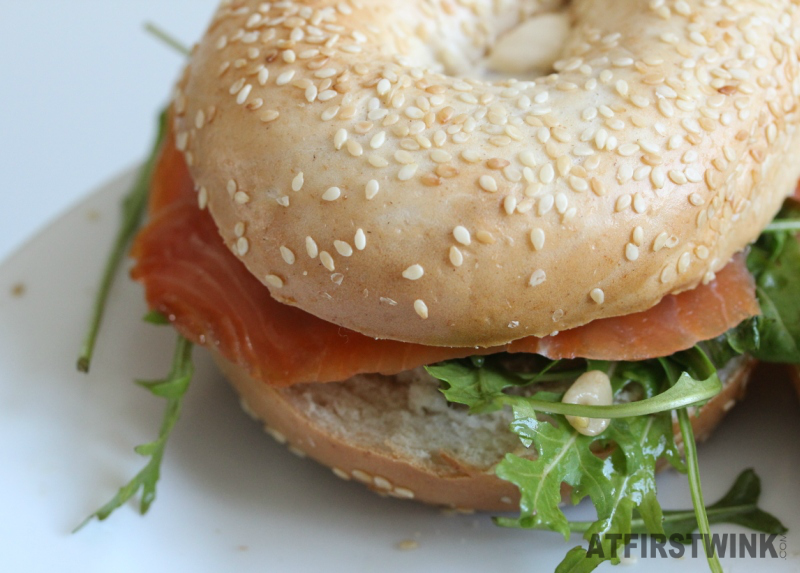 Bagel with smoked salmon rocket leaves pine nuts balsamic vinegar sesame oil dressing