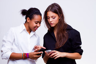 Two teenage girls checking their mobile phones