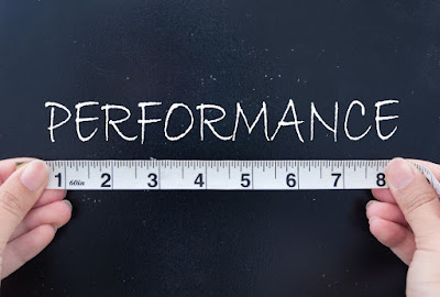 "a measuring tape is held under the word ""performance"""
