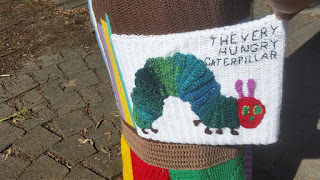Close-up of a book cover image, rendered in crochet, of 'The Very Hungry Caterpillar' by Eric Carle