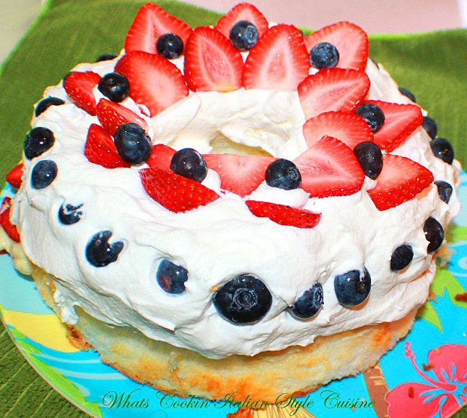 Red white and blue all decked out dessert with homemade angel food cake an Alton Browns Recipe along with a sugar free recipe decorated for the 4th of july in red white and blue fruits and whipped cream. Blueberries and strawberries on top for the 4th of July or Memorial Day Parties