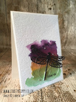 This image shows a handmade card featuring a dragonfly hovering over a water coloured background in green, yellow and purple, and is made entirely out of Stampin' Up! products such as the Detailed Dragonfly Thinlits Dies.