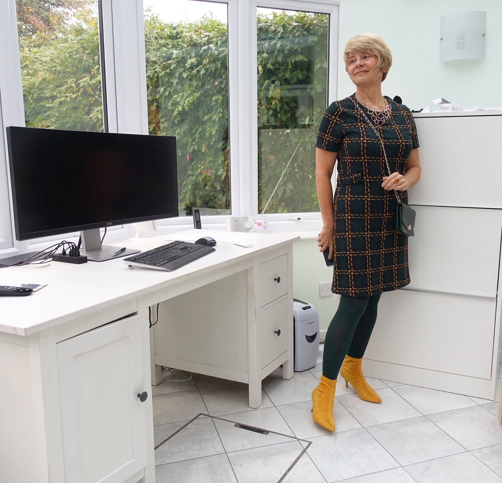 Posed in a home office, a work outfit from supermarket Sainsbury's: forest green and mustard dress worn with mustard ankle boots and a green cross-the-body bag