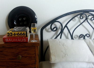One-twelfth scale modern miniature scene of a black iron bed with white embroidered bedding next to a wooden chest of drawers with a stack of design books and a glass of sparking wine on it.