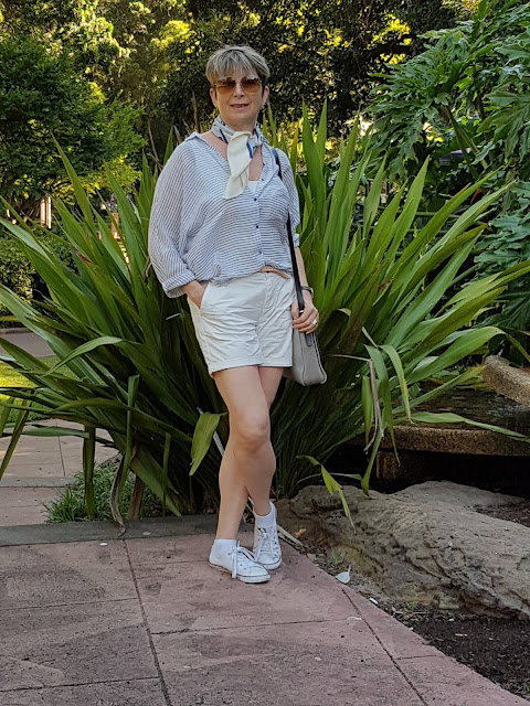 White shorts pared with sneakers, a blouse and vintage Pierre Cardin scarf