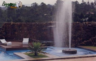 Execução da piscina com execução do chafariz com as paredes de pedras ornamentais e a execução do deck de madeira.