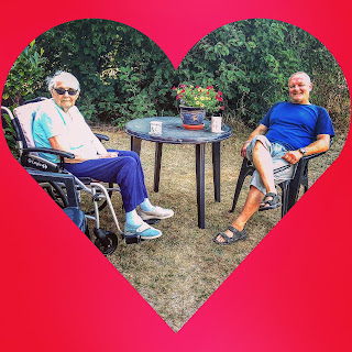 Granma Grace in her wheelchair, in the garden with Mr, her middle child. There's a garden table and cups of tea.