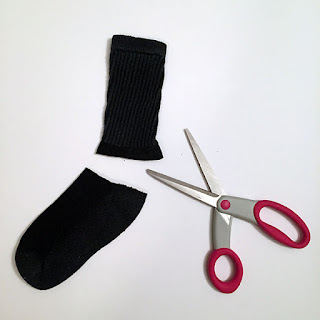Black sock cut by pink scissors