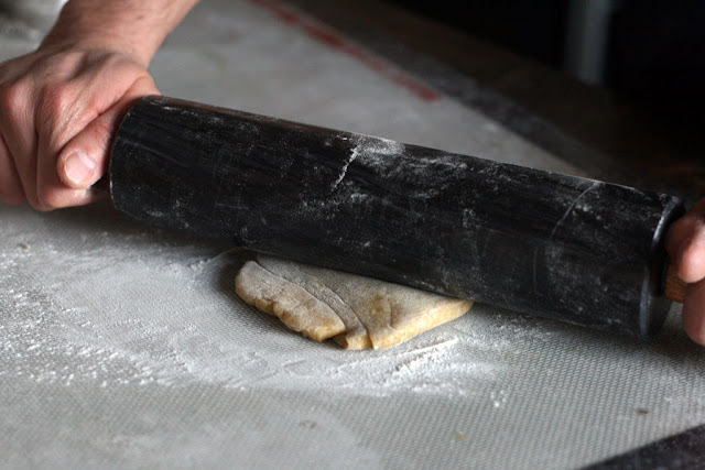 A rolling pin pressed against a flattened disc of dough.