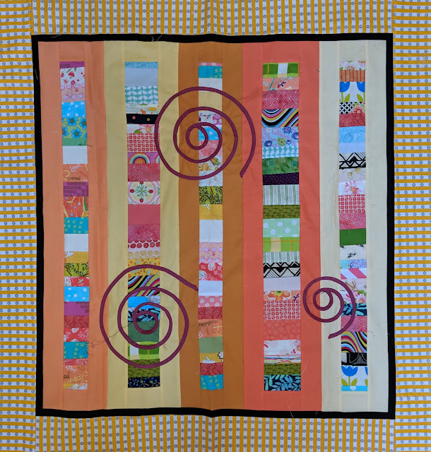 scrap quilt with yellow and ocher sashing and marsala spirals