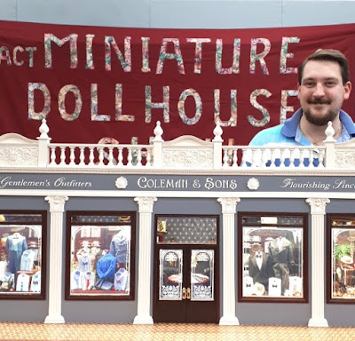 One-twelfth scale miniature gentlemen's outfitters shop, with 'Coleman & Sons' written above the door. Behind the model is a man and a fabric wallhanging that says 'ACT Miniature Dollshouse'.
