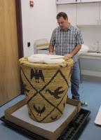 Tohono basket in the conservation lab for rehousing and support by art conservators. Shaun Pekar assists.