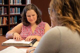 Studentė skaito knygą Brailio raštu