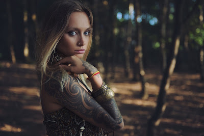 Linda chica rubia con tatuajes en el bosque