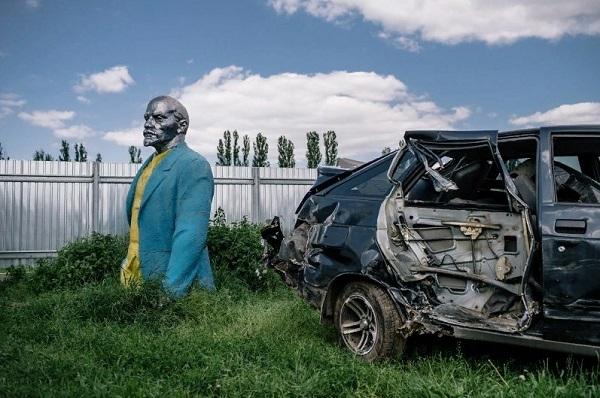 Imagen de la caída del comunismo en Ucrania: estatua de Lenin pintada de azul y amarillo junto a un auto abandonado.