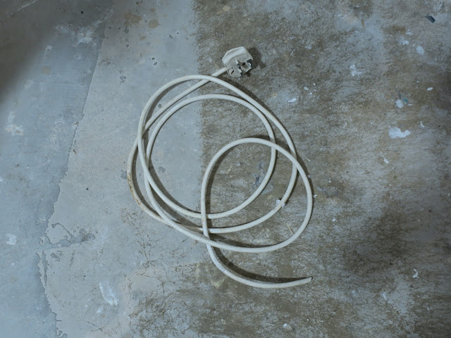 Plug and cut wire lying on concrete.